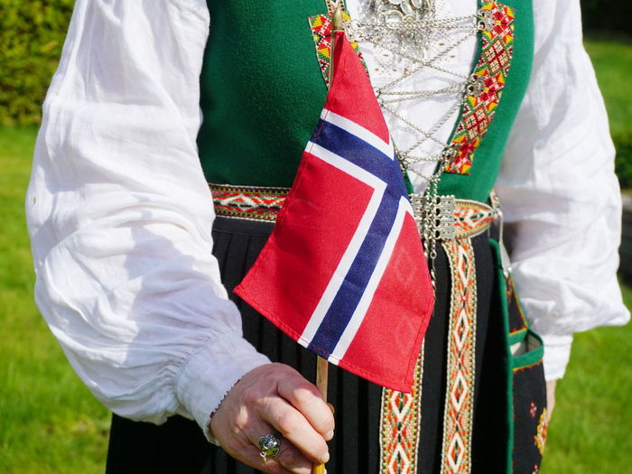 Midsection of woman wearing traditional clothing while holding norwegian flag