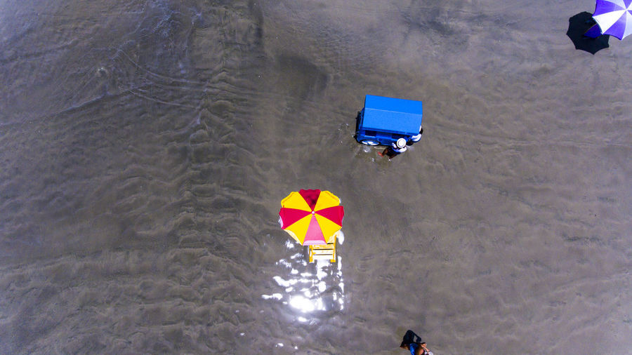 Drone picture from above showing beach umbrella and a blue cart. Beach Aerial View Brazil Drone  People Top Guarujá Summer Holiday Travel Tourism Leisure Tropical Sand Landmark Coast America Island South Destination Crowd Latin Latino Tourists Brazilian Umbrellas Pernambuco Shore Bay Popular Relax