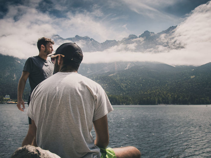 Rear view of man looking at lake against mountain range