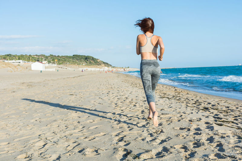 Full Length Of Young Woman Jogging On Sand At Beach Against Sky