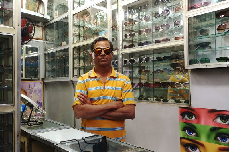 Portrait of man in sunglasses standing at store