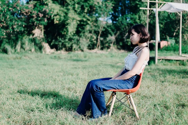 Side View Of Young Woman Sitting On Chair At Field