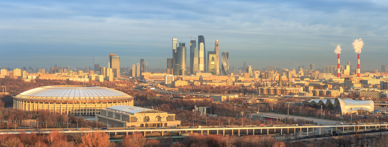 Cityscape of Moscow after sunrise with the financial district and the Luzhniki Stadium Golden Hour Sunrise Panorama Stadium Luzhniki Moscow Financial District  Landscape Modern Outdoors Urban Skyline Travel Destinations Tall - High Cloud - Sky Tower Skyscraper Office Building Exterior Cityscape Sky Building City Building Exterior Architecture Built Structure