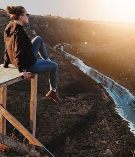 Woman sitting on table against land during sunset