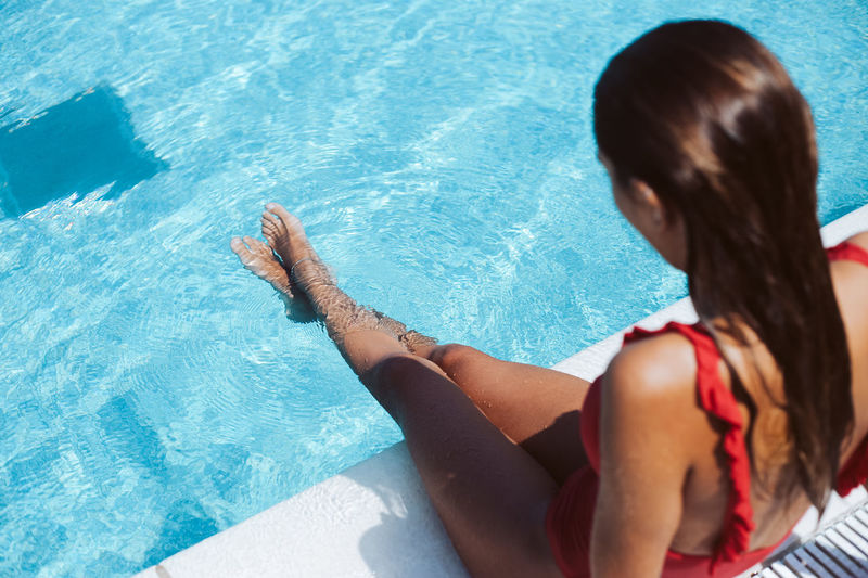 Rear view of woman sitting at swimming pool