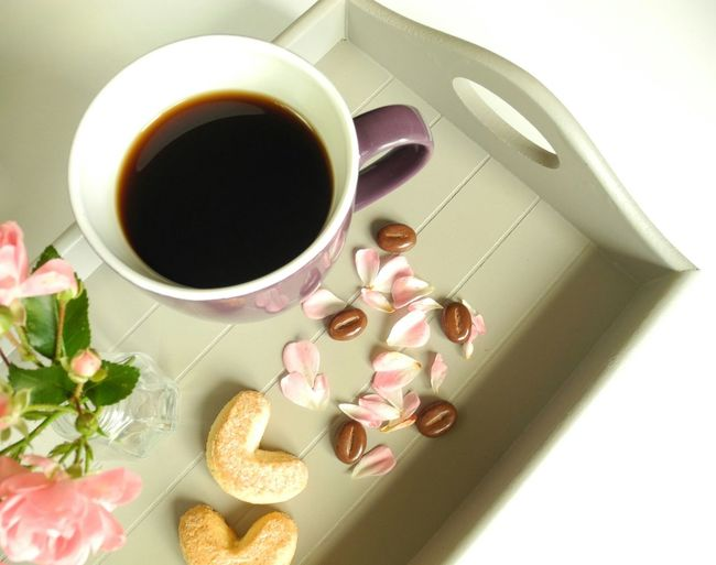 High Angle View Of Black Coffee With Cookies And Flower Vase On Table