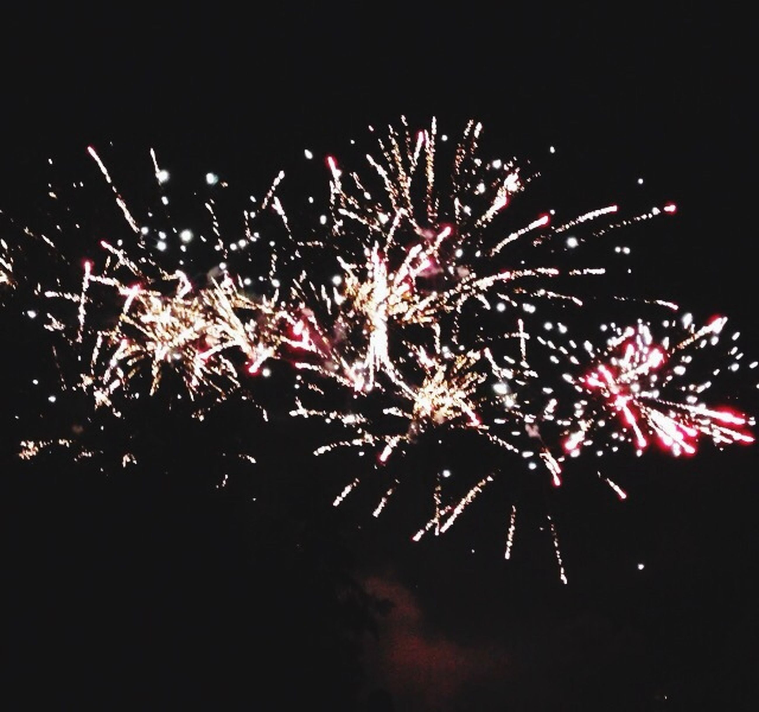 night, firework display, celebration, exploding, illuminated, long exposure, firework - man made object, arts culture and entertainment, event, motion, sparks, firework, glowing, entertainment, blurred motion, sky, low angle view, multi colored, celebration event, fire - natural phenomenon