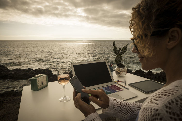 beautiful assistant professional lady at work in alternative freedom concept office in front to the ocean. enjoy a different lifestyle and work with social media like digital nomad Canary Islands Office Adult Beautiful Woman Cloud - Sky Communication Computer Connection Enjoyment Glass Headshot Horizon Over Water Laptop Nature One Person Outdoors Sea Sky Table Technology Tenerife Using Laptop Using Mobile Phone Water Wireless Technology