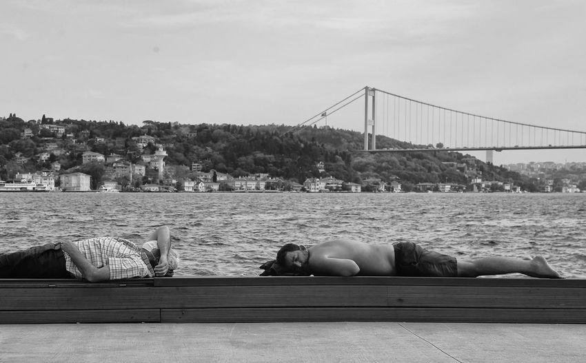 Man resting on bridge against sky