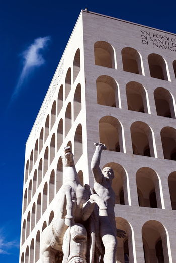 Low angle view of statue against building against sky