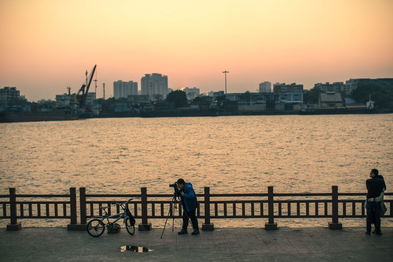 sunset, railing, built structure, water, architecture, building exterior, city, men, sea, sky, outdoors, real people, two people, skyscraper, full length, silhouette, leisure activity, city life, cityscape, urban skyline, nature, lifestyles, women, togetherness, clear sky, beauty in nature, day, people