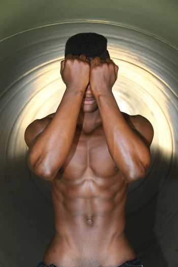 Shirtless young man with hands covering face standing against wall