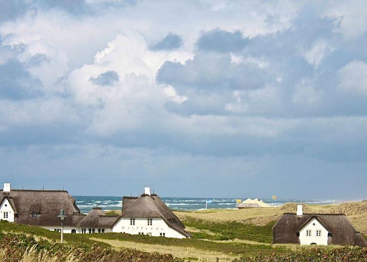Built structure  on coastline against cloudy sky