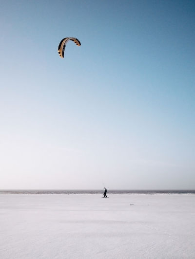 Person kiteboarding on snowcapped beach during winter