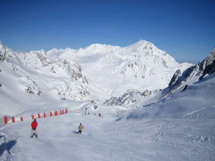 People skiing in mountains against clear sky