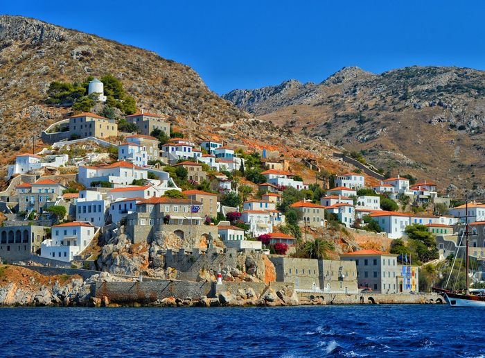 Town by sea against sky at hydra island