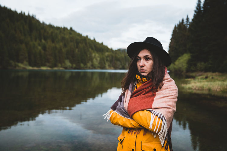 Woman looking away while standing by lake
