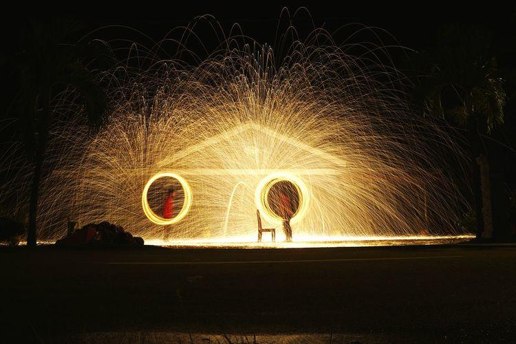 Full length of illuminated man standing against sky at night