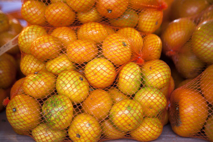 Close-up of tangerines and persimmons in netting for sale at market
