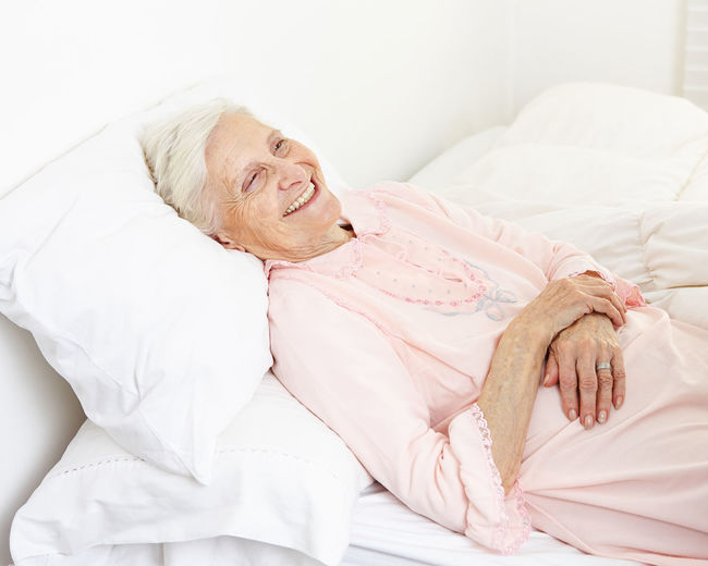 Smiling senior woman lying on bed at hospital