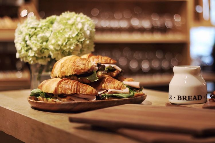 Sandwiches served on table by flower pot