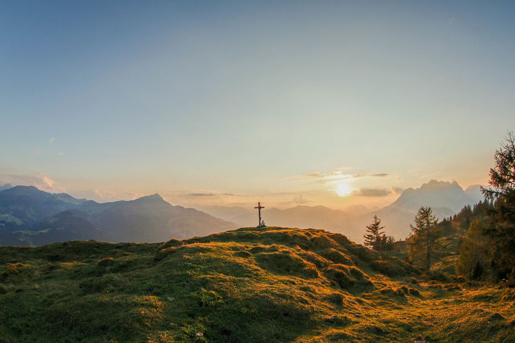 Scenic view of cross on a  hill in the mountains against clear sky