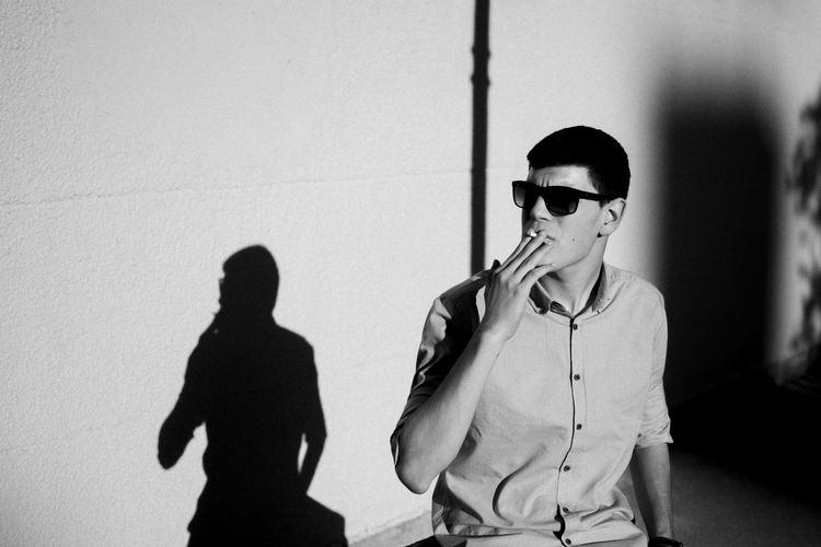 Young man wearing sunglasses smoking cigarette against wall during sunny day