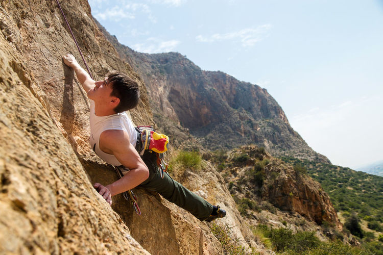 Young woman with arms raised on cliff against sky