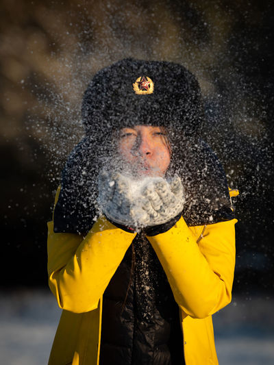 Close-up of person wearing hat standing during winter