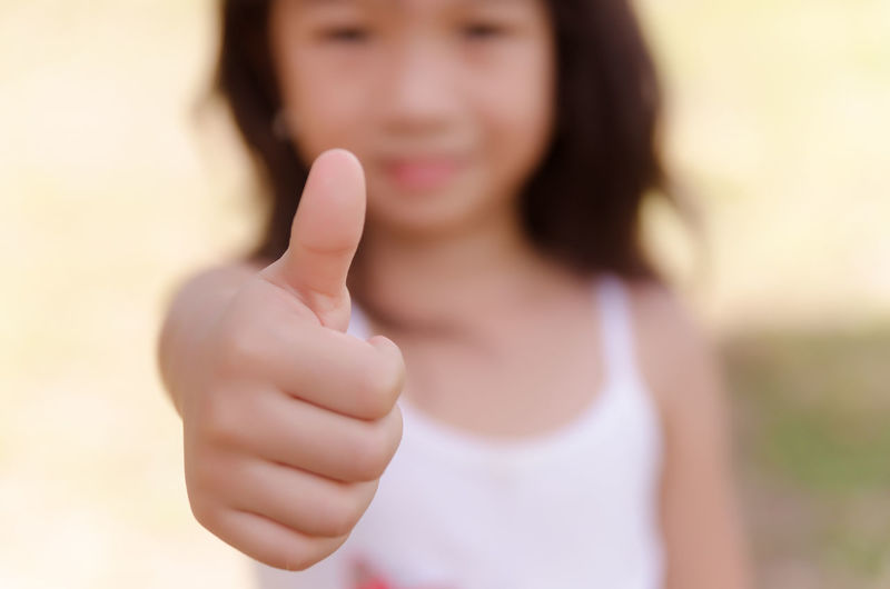 Portrait of girl gesturing thumbs up