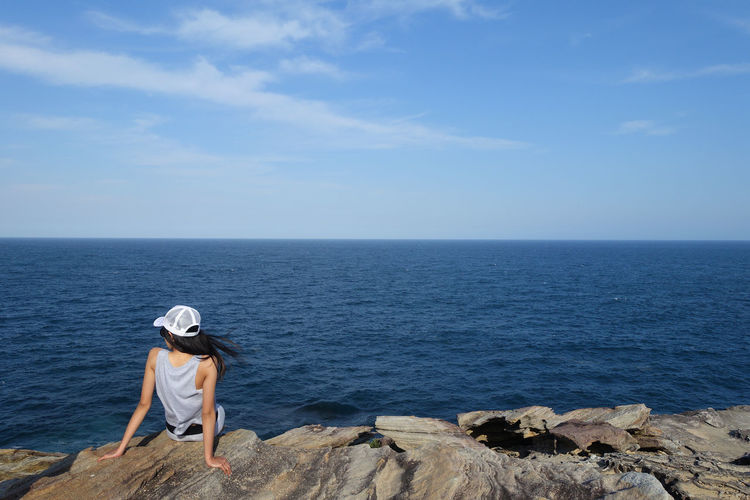 Young Asian girl in cap sits on a high stone hill facing blue sea Blue Sea Adult Adventure Balconies Beach Beauty In Nature Full Length Horizon Over Water Leisure Activity Nature One Person One Woman Only Outdoors People Rear View Royal National Park Scenics Sea Sky Tranquil Scene Tranquility Vacations Water Women Young Adult The Traveler - 2018 EyeEm Awards The Great Outdoors - 2018 EyeEm Awards