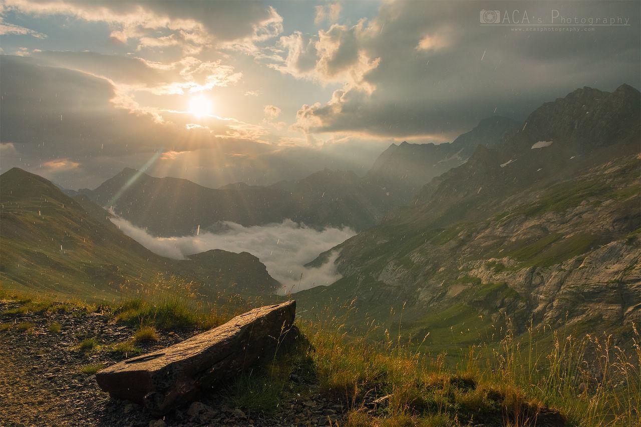 mountain, beauty in nature, sky, scenics - nature, tranquility, tranquil scene, cloud - sky, mountain range, environment, landscape, non-urban scene, sunbeam, nature, sun, sunlight, idyllic, no people, sunset, lens flare, outdoors, mountain peak
