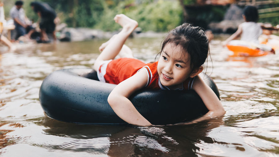 Smiling girl relaxing on inflatable ring floating in lake