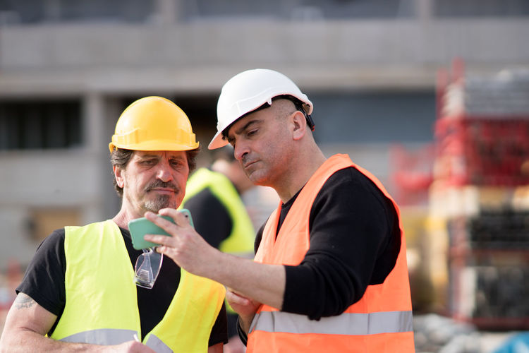 Workers using phone at construction site
