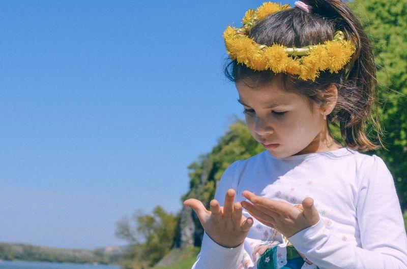 Girl standing against blue sky