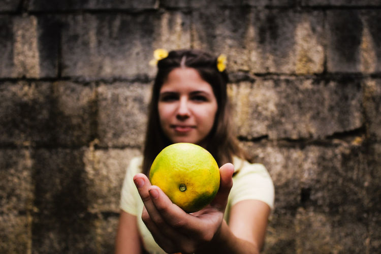Young woman holding orange fruit against wall