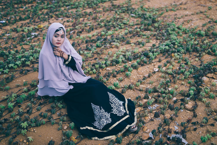 Portrait Young Women Sitting Field Looking At Camera Outdoors Person Hijab Fashion Non-urban Scene Rural Scene Day Alone People People And Places Mood Girl Nature Young Adult Warm Clothing Autumn Fashionable The Portraitist - 2018 EyeEm Awards International Women's Day 2019
