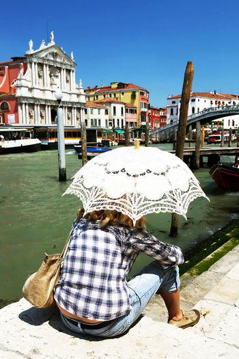 Woman carrying white umbrella looking at santa maria di nazareth while resting by grand canal
