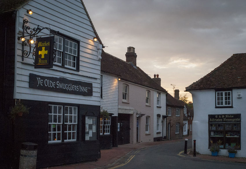 The village of Alfriston in East Sussex, England. Alfriston East Sussex Pub Architecture Britian Building Building Exterior Built Structure City Cloud - Sky Communication Dusk England Information Nature No People Olde English Outdoors Residential District Road Sign Sky Smuggler Smuggling Street Text Transportation Village Wealden Western Script Window