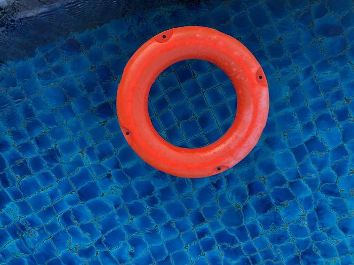 Life buoy loop floating in the blue swimming pool EyeEm Selects Blue Circle Geometric Shape Shape No People Orange Color Red High Angle View Life Belt Directly Above Safety Design Protection Outdoors Tubing Close-up Day Security Still Life Floating On Water