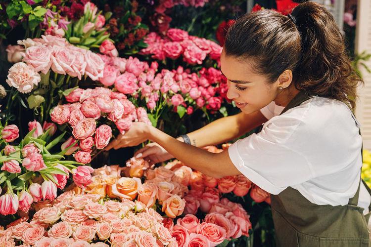 Florist examining roses in flower shop