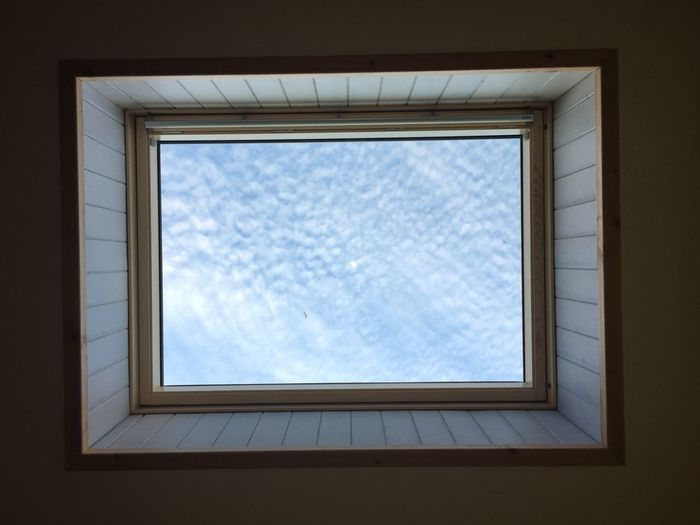 Directly below shot of skylight against cloudy sky