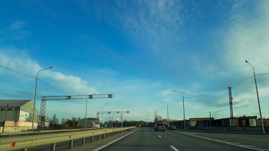 Vehicles on road against blue sky