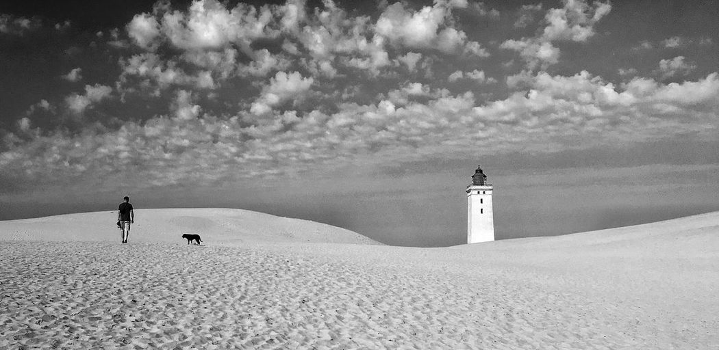 People on beach by lighthouse against sky