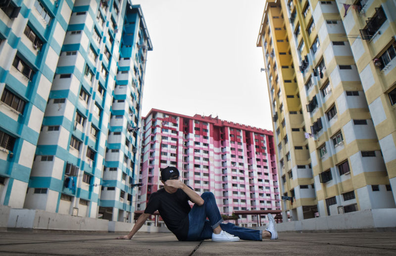 Rear view of man sitting against buildings in city