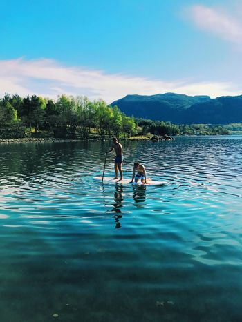 Two People Water Togetherness Real People Day Leisure Activity Sky Childhood Nature Full Length Outdoors Lake Bonding Waterfront Boys Fun Tree Men Rippled Vacations Live For The Story Live For The Story