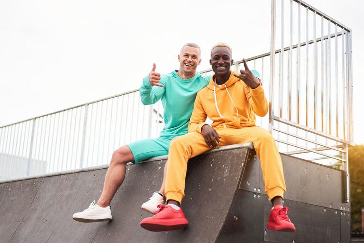 Portrait of happy friends sitting on railing