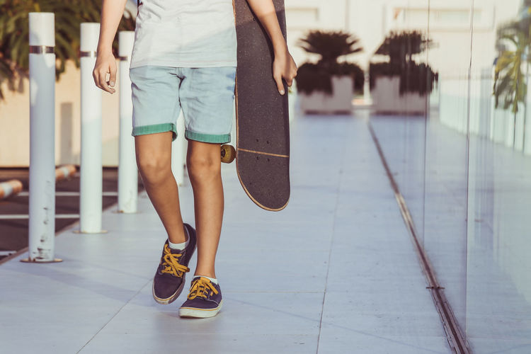 Low section of boy walking with skateboard on floor