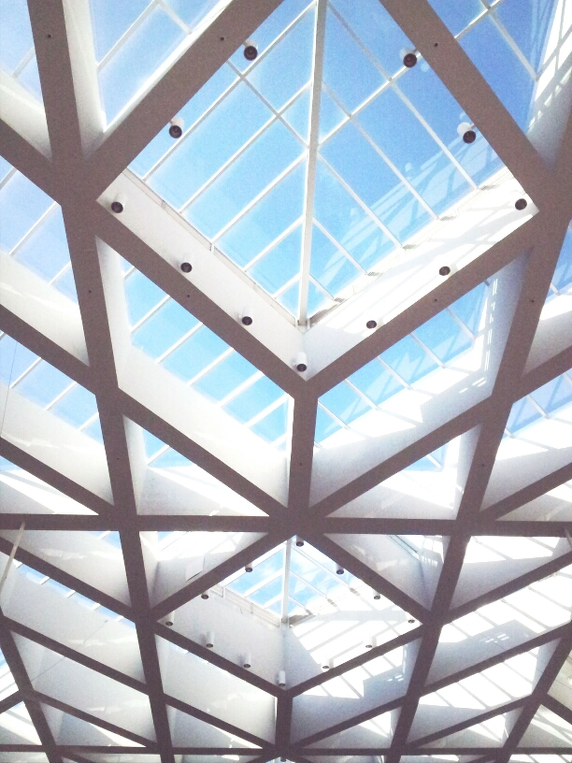 indoors, architecture, low angle view, ceiling, glass - material, built structure, pattern, modern, skylight, architectural feature, geometric shape, transparent, full frame, design, window, directly below, glass, backgrounds, day, sky