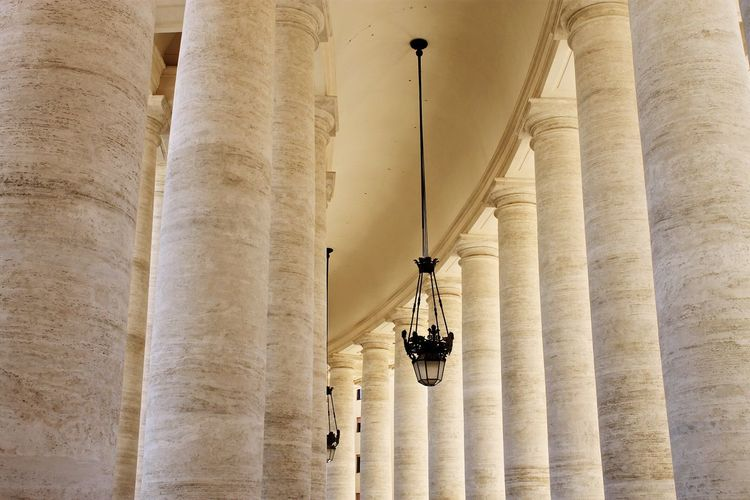 Low Angle View Of Lamp Hanging Amidst St Peters Square Columns